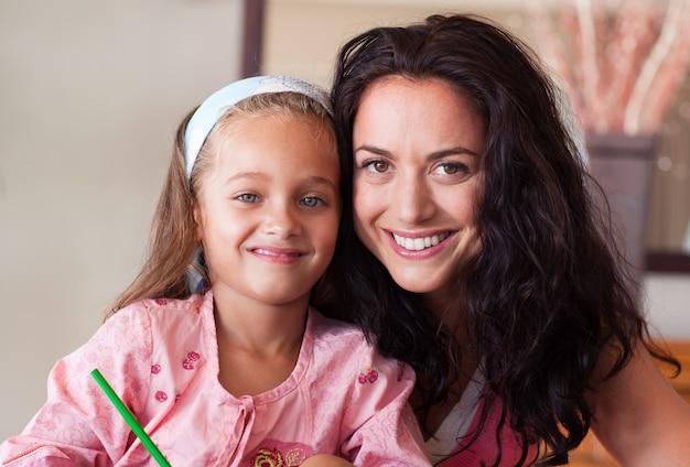 Mãe feliz, ajudando a filha para o dever de casa