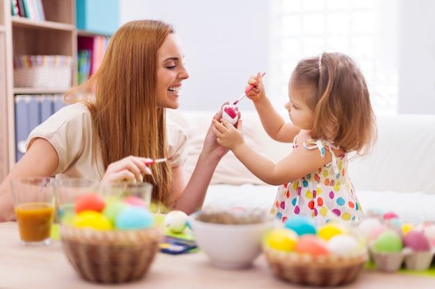 Mãe feliz ajudando bebê pintando ovos de páscoa