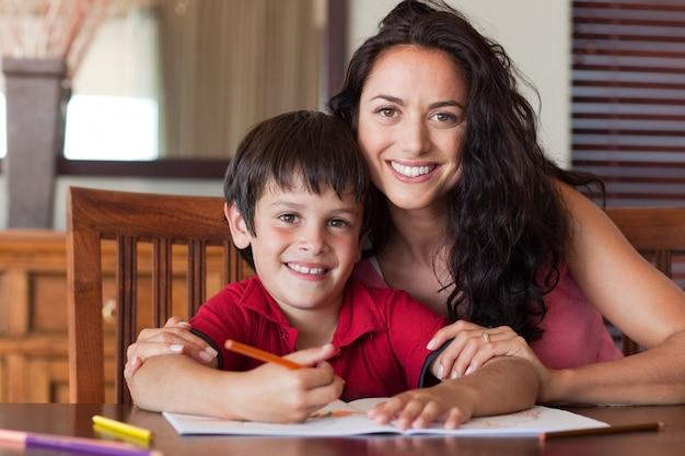 Mãe feliz ajudando seu filho para a lição de casa