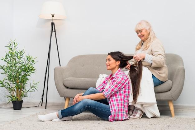 Mãe feliz, amarrando o cabelo da filha sentada no tapete