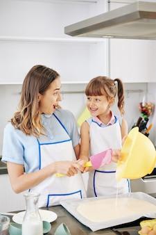 Mãe feliz animada e filha pré-adolescente olhando uma para a outra enquanto colocam a massa líquida que fizeram na assadeira