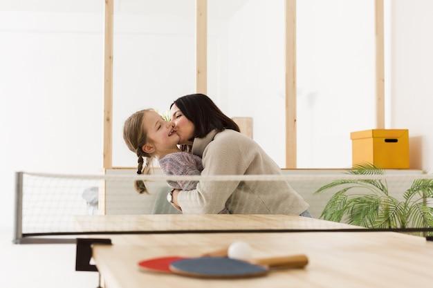 Mãe feliz, beijando a filha dentro de casa