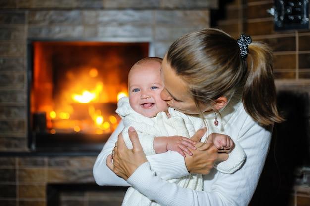 Mãe feliz beijando a menina à beira da lareira