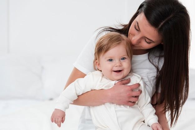 Mãe feliz beijando bebê