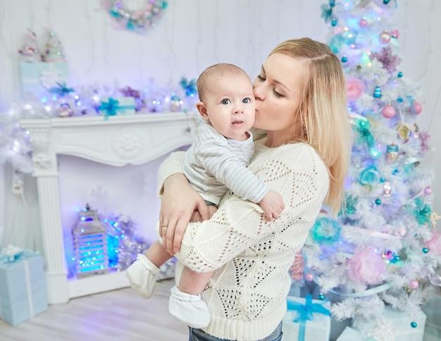 Mãe feliz beijando seu bebê perto da árvore de natal. o conceito de natal