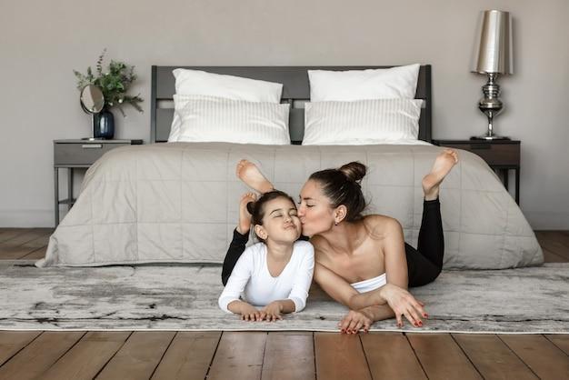 Mãe feliz beijando sua filhinha em casa deitada no chão no fundo da cama