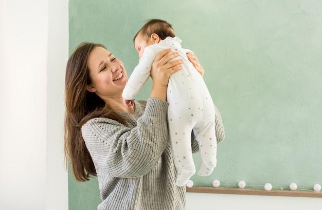 Mãe feliz brincando com bebê fofo
