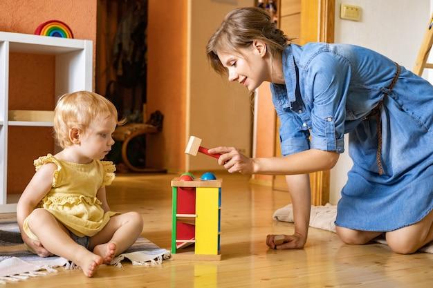 Mãe feliz brincando de criança batendo martelo de madeira em bolas coloridas, brinquedo ecológico de desenvolvimento inicial