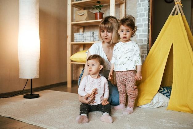 Mãe feliz brincando no chão com duas meninas gêmeas. cabana amarela