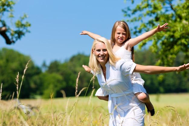 Mãe feliz, carregando a filha nas costas na natureza