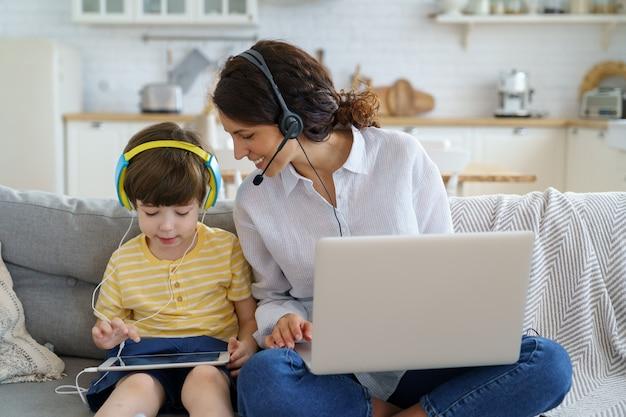 Mãe feliz com a criança sentada no sofá em casa durante o trabalho de bloqueio no laptop, criança brincando no tablet