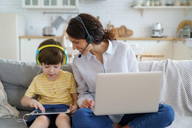 Mãe feliz com a criança sentada no sofá em casa, trabalhando no laptop, criança brincando no tablet