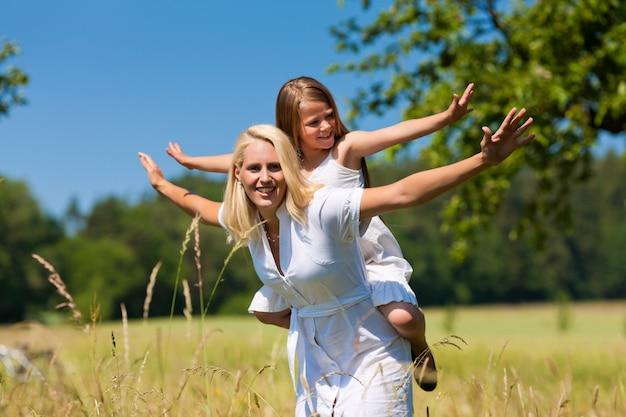 Mãe feliz com a filha nas costas ao ar livre