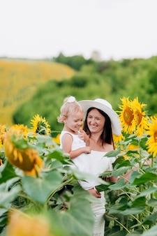 Mãe feliz com a filha no campo com girassóis. mãe e bebê se divertindo ao ar livre. conceito de família. foco seletivo