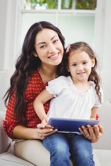 Mãe feliz com a filha segurando um tablet digital em casa