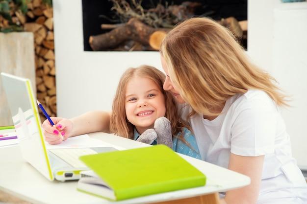 Mãe feliz com a filha sentada na sala de estar e desenhando juntos