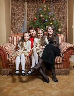 Mãe feliz com as filhas sentadas no sofá na véspera de natal