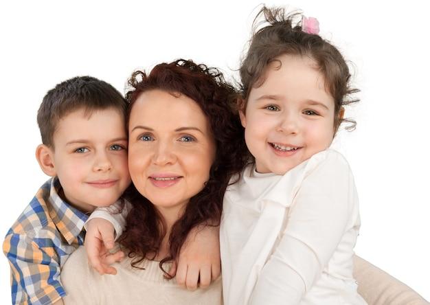 Mãe feliz com filha e filho se abraçando no fundo