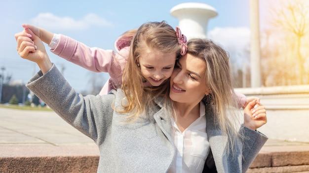 Mãe feliz com filha posando ao ar livre