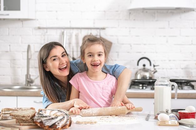 Mãe feliz com filha preparando bolos caseiros no fundo de uma cozinha leve.