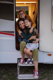 Mãe feliz com filhas de carro ao ar livre em acampamento ao entardecer, viagem de férias em família de caravana.