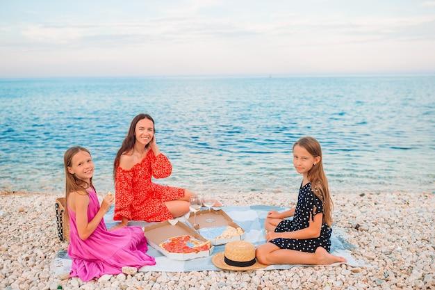 Mãe feliz com filhos na praia fazendo piquenique