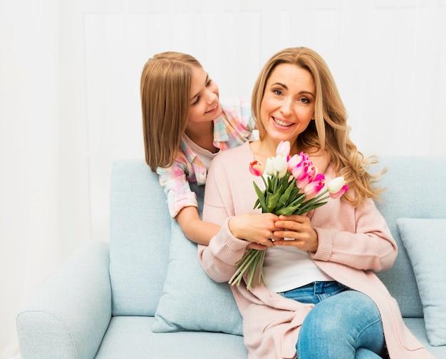 Mãe feliz com flores da filha