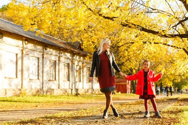 Mãe feliz com folhetos de bordo amarelo abraça a filha na floresta de outono. profundidade superficial de campo.