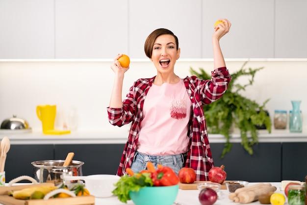 Mãe feliz com laranjas frescas nas mãos, vestindo uma camisa xadrez com um penteado curto cozinhando