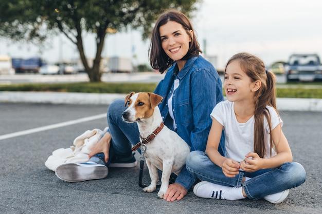 Mãe feliz com menina e cachorro