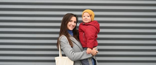 Mãe feliz com seu filho sorridente em um fundo cinza