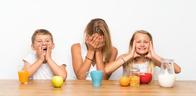 Mãe feliz com seus dois filhos tomando café da manhã