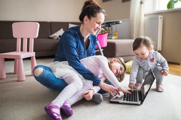Mãe feliz com seus filhos trabalhando no laptop