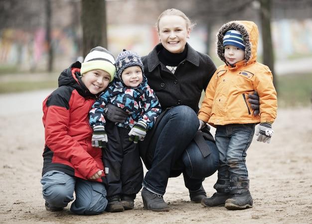 Mãe feliz com seus três filhos