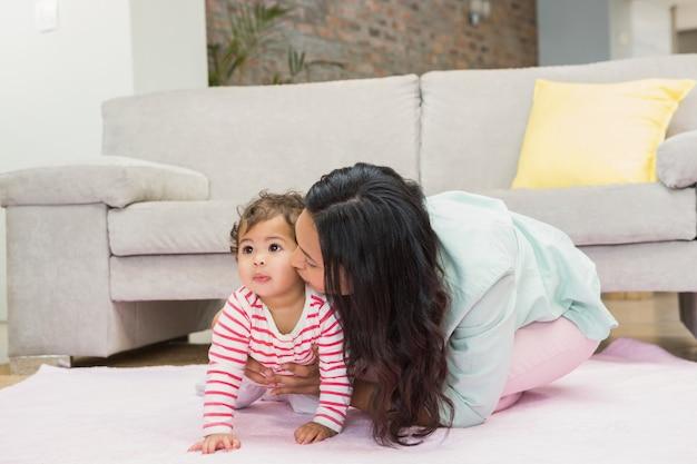 Mãe feliz com sua filha bebê no tapete na sala de estar