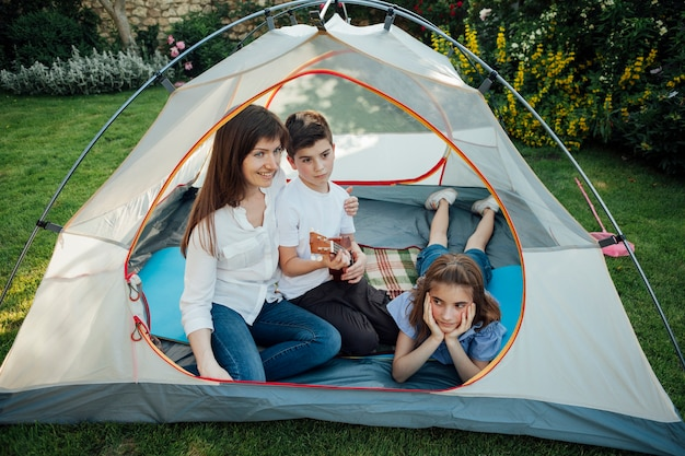 Mãe feliz com sua filha e filho na tenda na grama no parque