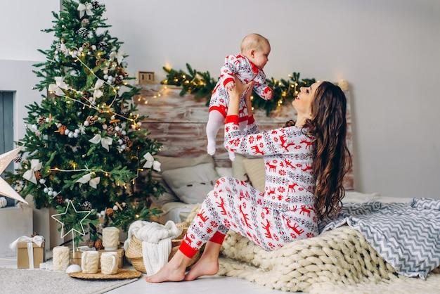 Mãe feliz com sua filha em roupas de férias com veados impressos e flocos de neve se divertindo na cama na acolhedora sala com uma árvore de natal e luzes de natal. ano novo e o conceito de natal.