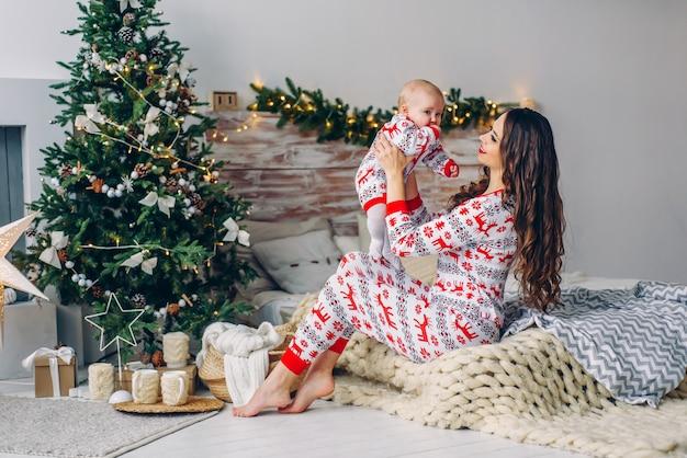 Mãe feliz com sua filha em roupas de férias com veados impressos e flocos de neve se divertindo na cama no quarto acolhedor