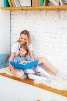 Mãe feliz com sua filha lendo um livro e sorrindo enquanto está sentada no chão da sala de estar