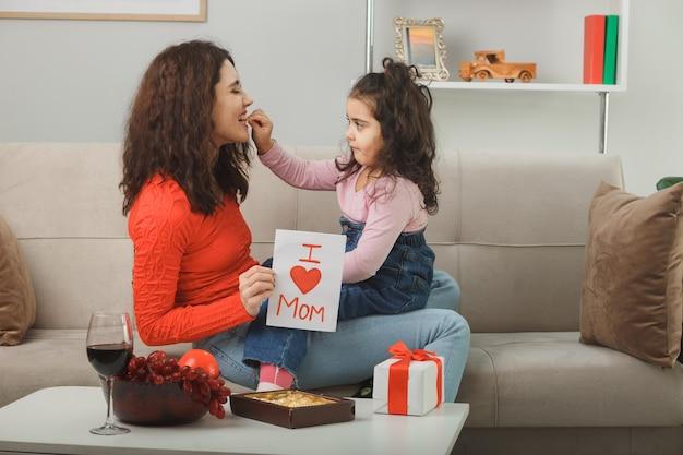 Mãe feliz com sua filha pequena sentada em um sofá segurando um cartão de felicitações para o dia das mães