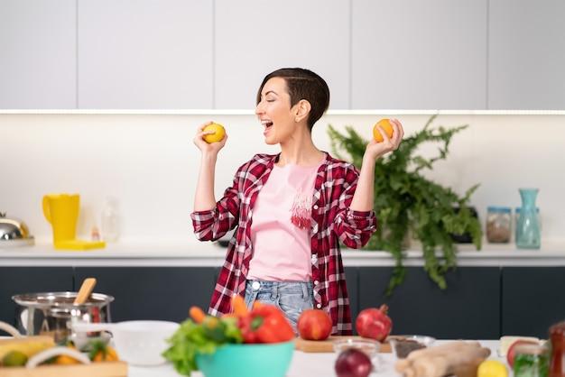 Mãe feliz com tomates frescos amarelos nas mãos, vestindo uma camisa xadrez com um penteado curto cozinhando