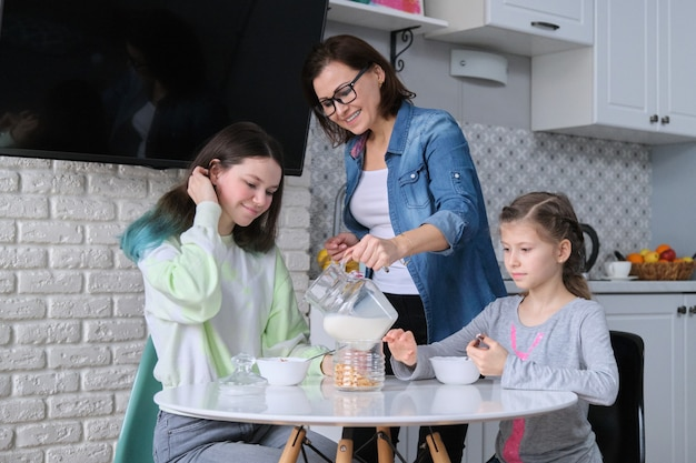 Mãe feliz cuidando das filhas na cozinha