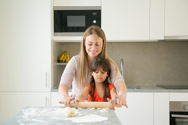 Mãe feliz e a filha dela curtindo o tempo juntos, rolando massa na mesa da cozinha com farinha em pó.