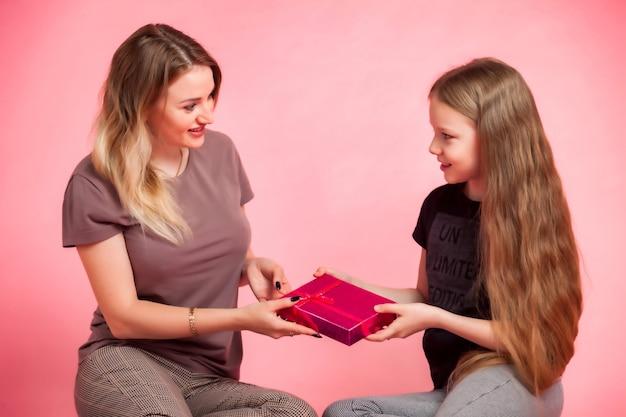 Mãe feliz e a filha em roupas casuais, com caixa de presente no fundo rosa. conceito para celebrar o dia das mães ou o dia da mulher, passando um tempo junto com os filhos e os relacionamentos familiares