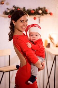 Mãe feliz e adorável bebê com chapéu de papai noel celebram o natal
