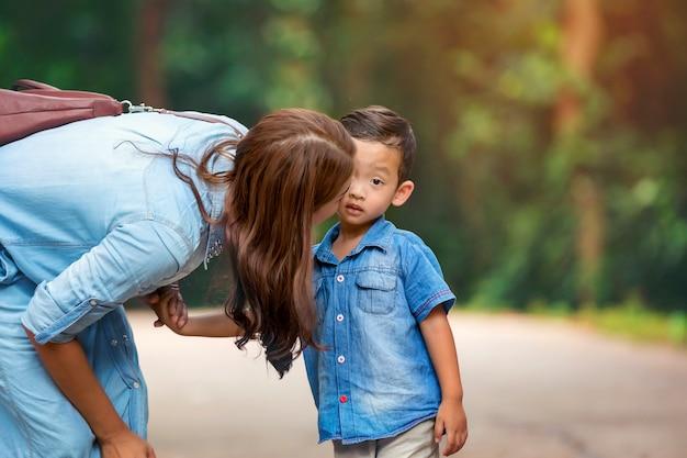 Mãe feliz e adorável garotinho, aproveitando o clima quente no belo parque