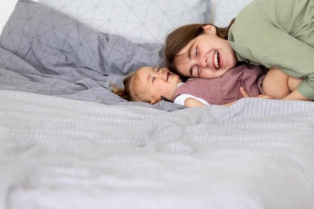 Mãe feliz e criança na cama