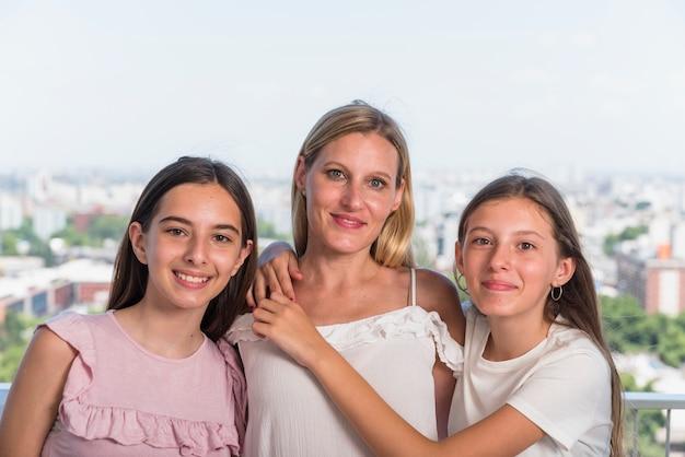 Mãe feliz e duas filhas abraçando