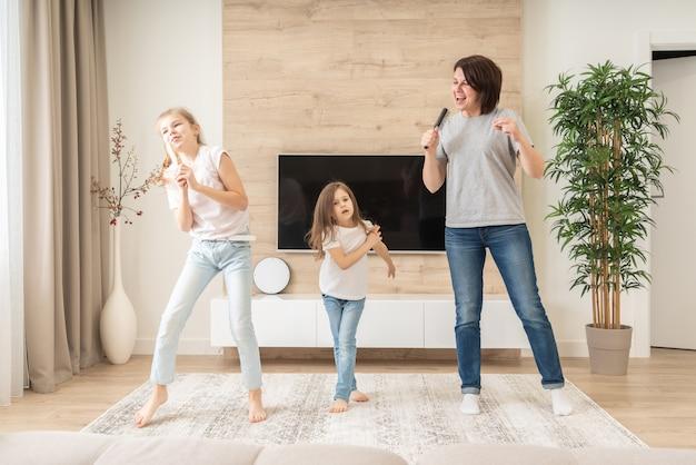 Mãe feliz e duas filhas se divertindo cantando música de karaokê em escovas de cabelo. mãe rindo desfrutando de atividade estilo de vida engraçado com adolescente em casa juntos.