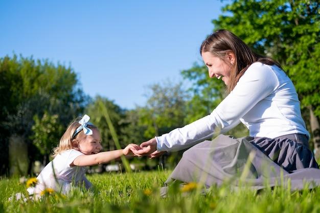 Mãe feliz e filha brincando se divertindo ao ar livre no parque no verão.